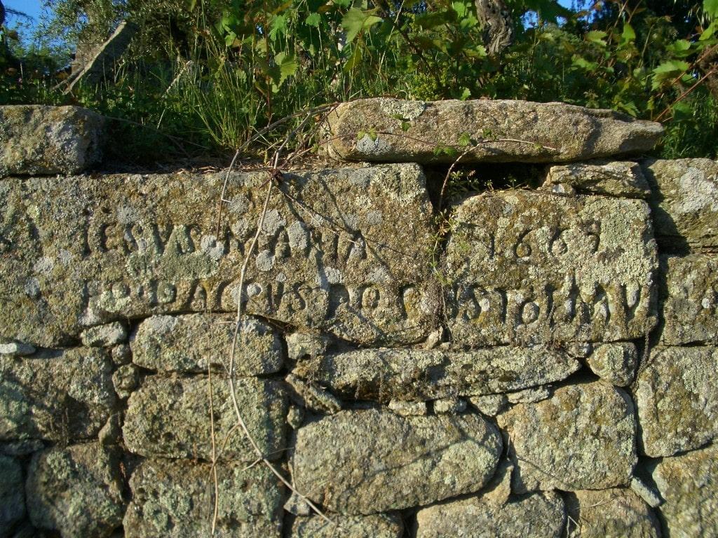 Inscrição em pedras no muro situada à direita do escadório para a ermida de Nossa Senhora de Cervães.